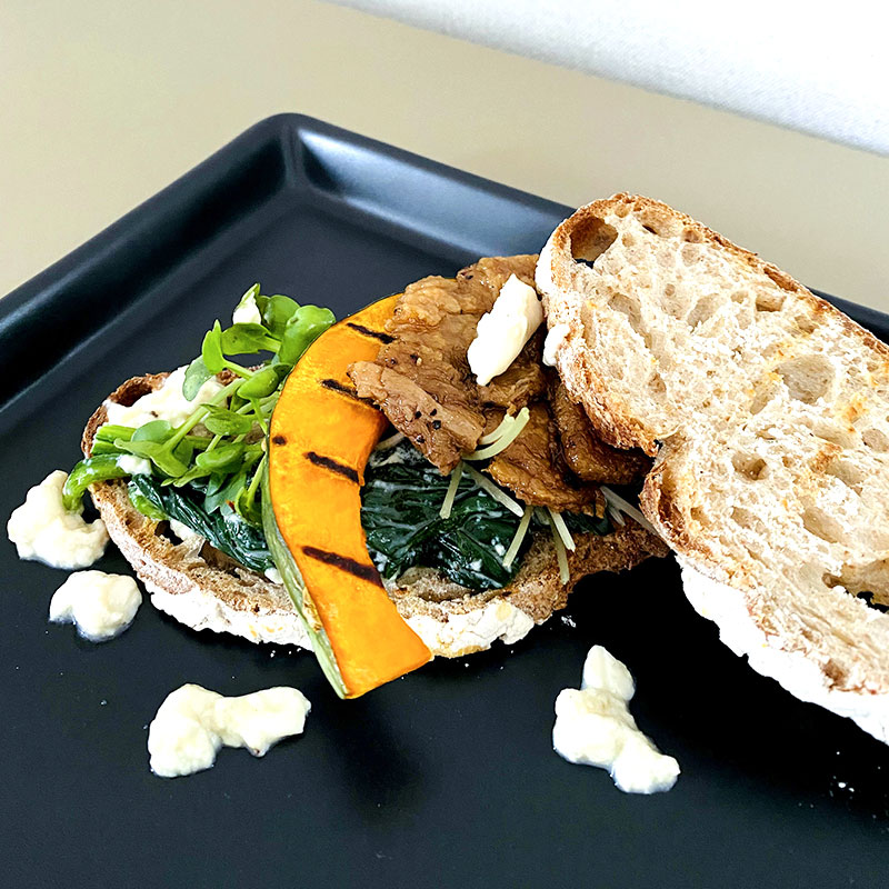 Transfer some Yubayose tofu - spinach paste on the bread. Add sprouts and grilled pumpkin slice. On the top add larger slices of SoMeat - Aburiyaki.