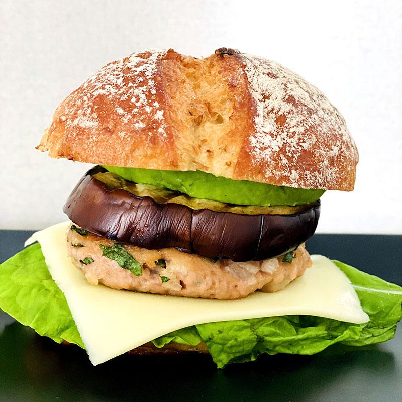 Spread Dijon mustard on the bun and add lettuce, cheese, Iburi-gakko and Shiso cutlet, eggplant, avocado slice.