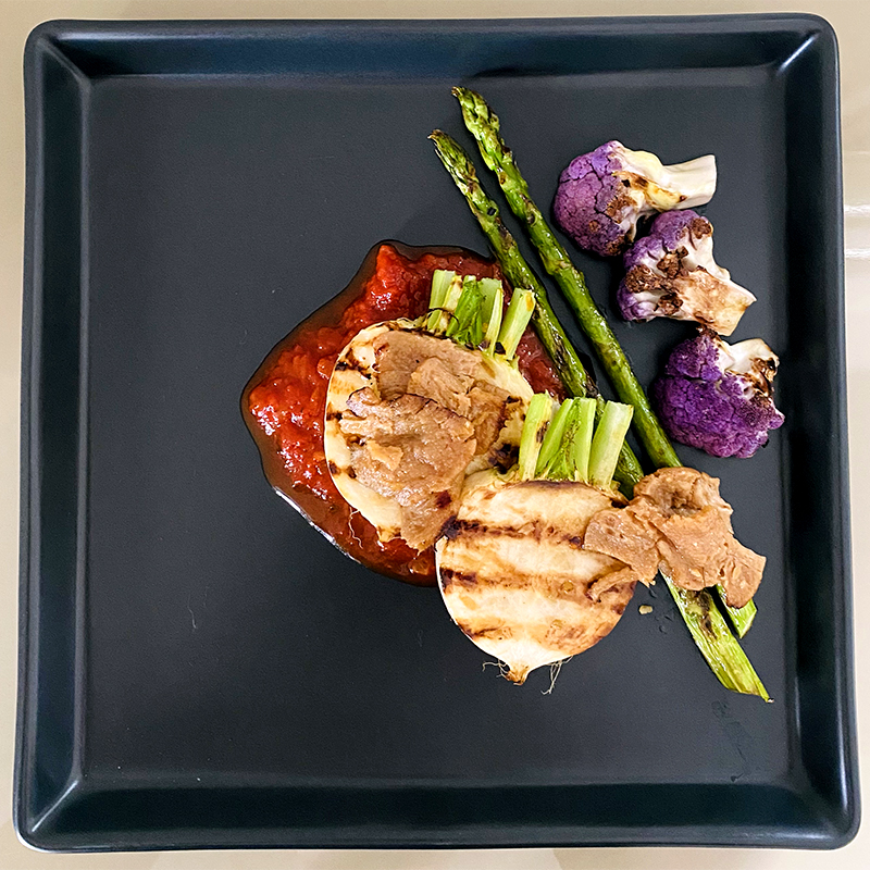 Transfer tomato sauce onto the plate and then asparagus,turnip,cauliflower and SoMeat.