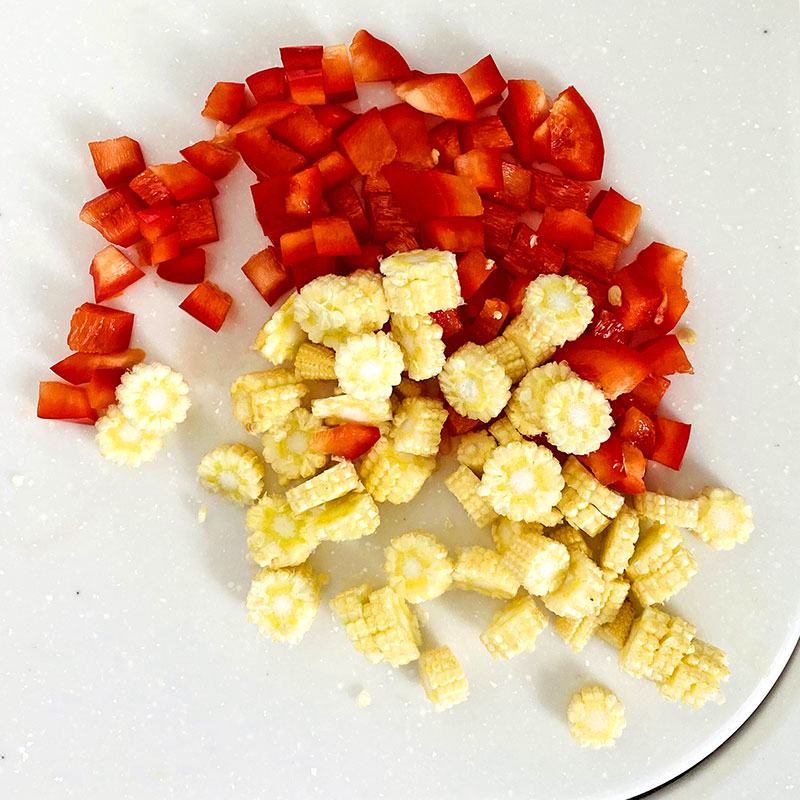 Chop the baby corn and red pepper.