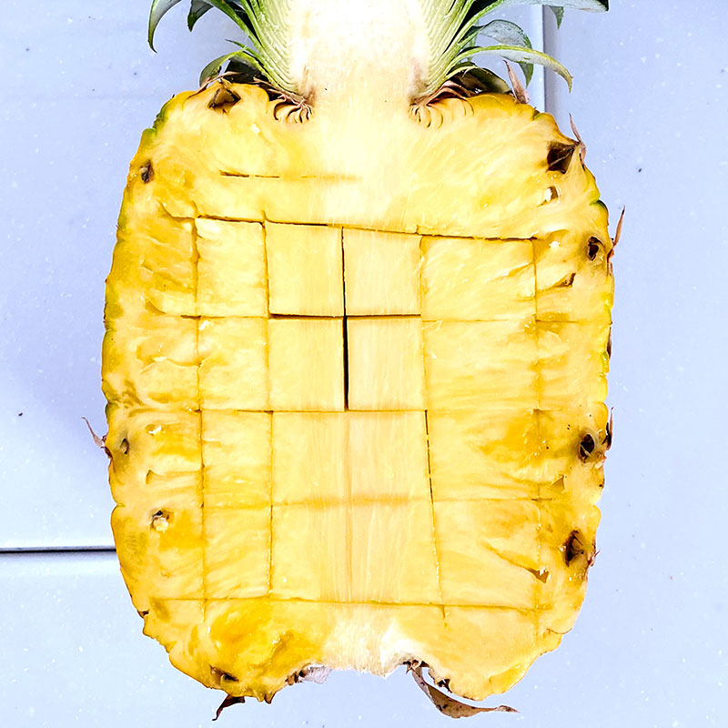 Halve the pineapple and cut it into a bite size squares.