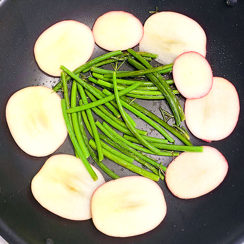 Add the sliced apple to the pan with the green beans and turn on the heat.