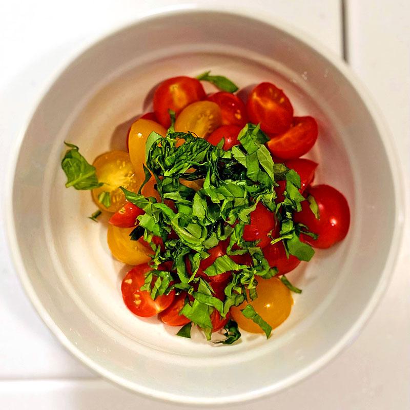 ボウルに切ったトマトを入れ、刻んだバジルを加え、混ぜる。
